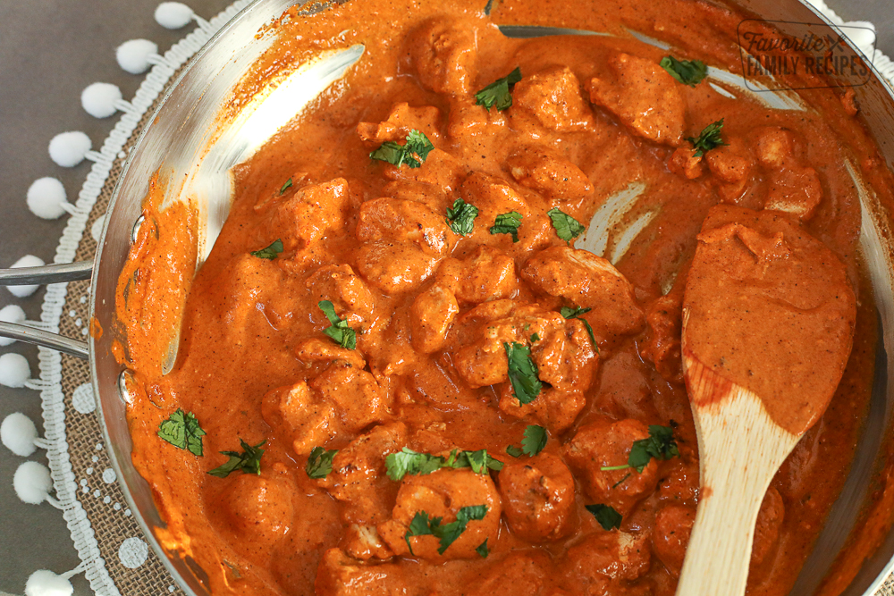 Chicken Tikka Masala cooking in a large skillet and stirred with a wooden spoon.