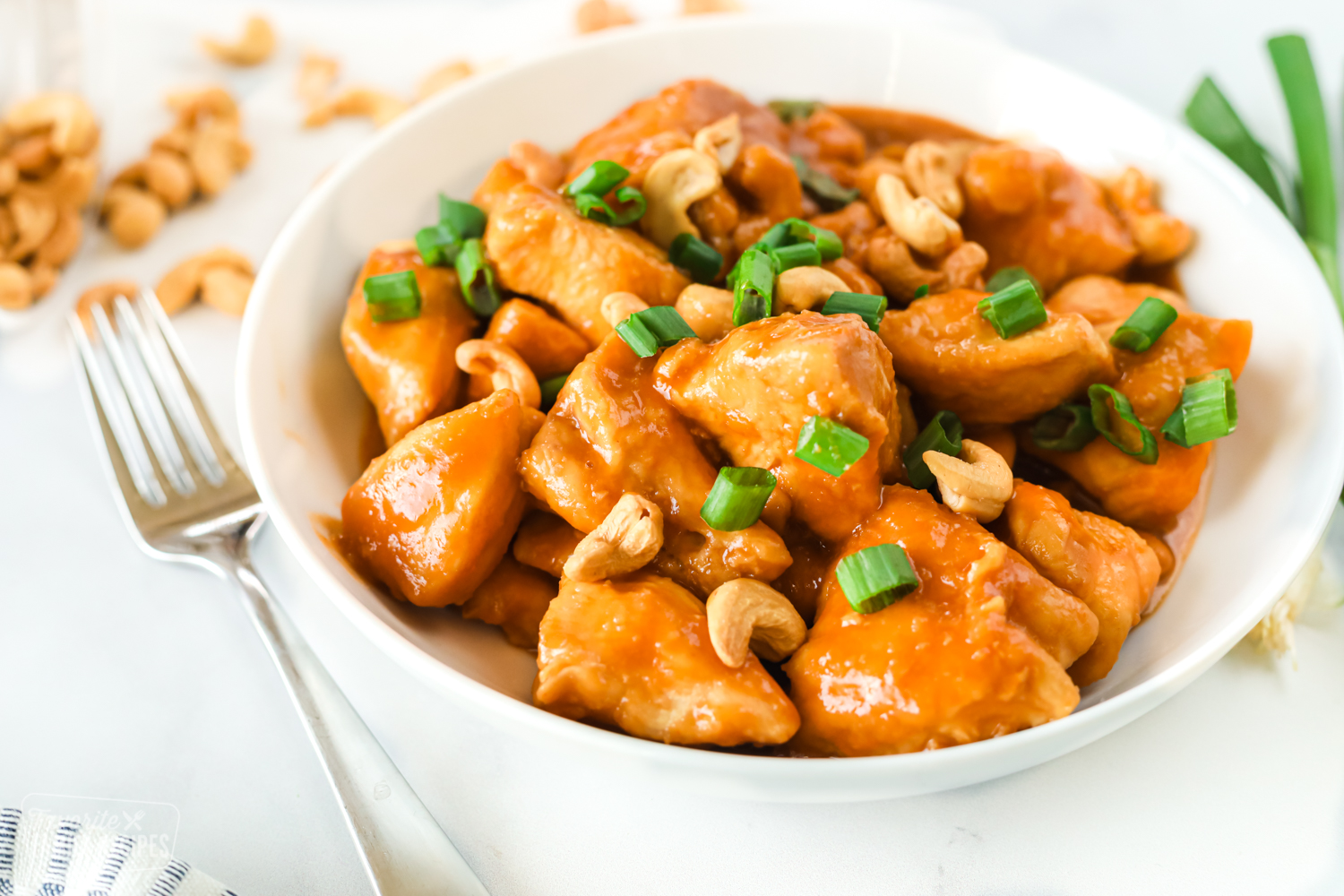 A bowl of cashew chicken with cashews, sauce, and green onion