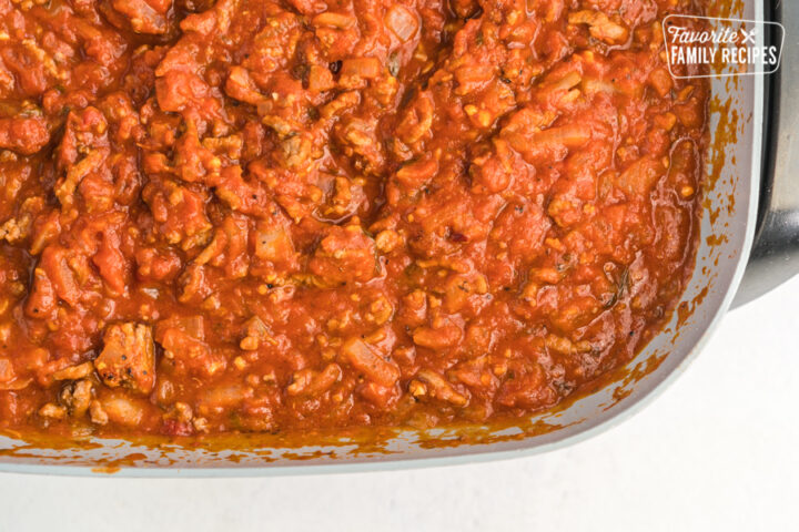 Tomato sauce, ground beef, and onions cooked in a skillet