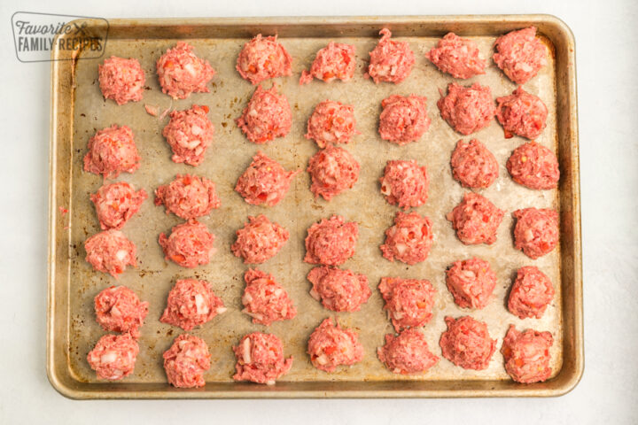 Uncooked meatballs lined up on a baking sheet