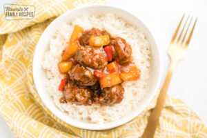 A bowl of rice topped with sweet and sour meatballs