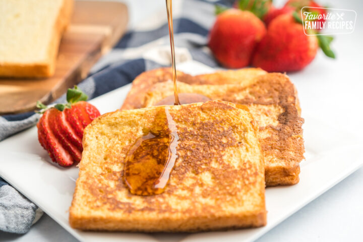 Maple syrup being poured onto a plate of french toast slices