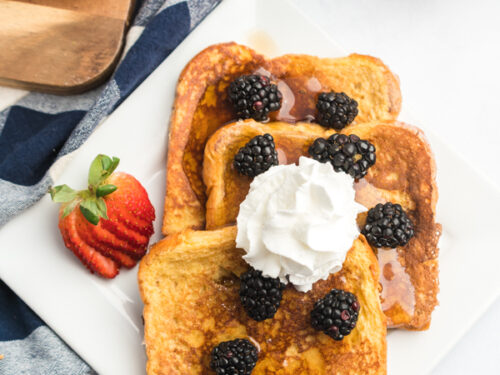 A plate of French toast slices topped with blackberries, syrup and whipped cream