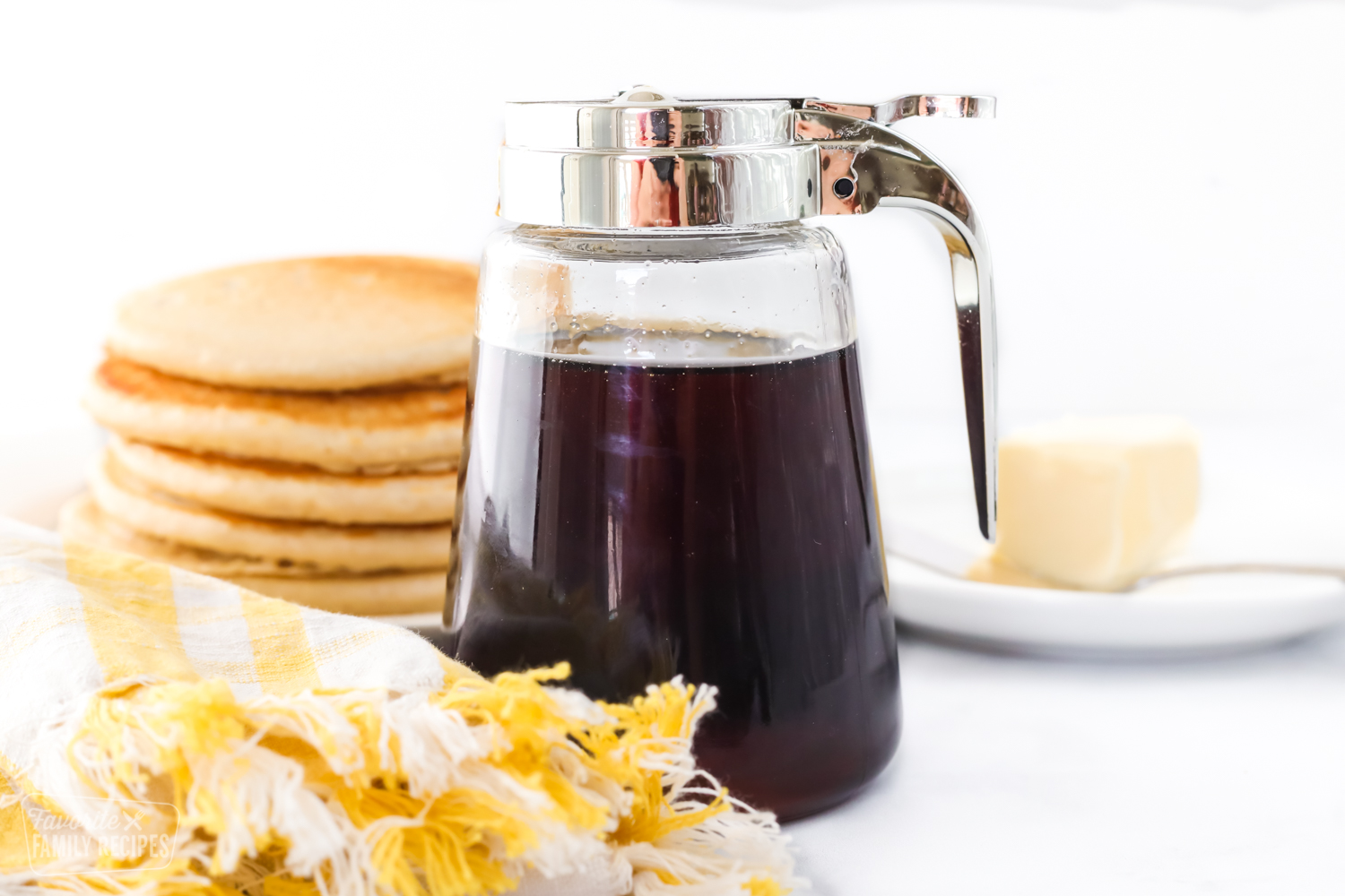 Homemade syrup in a jar with a lid and pour spout next to a stack of breakfast pancakes