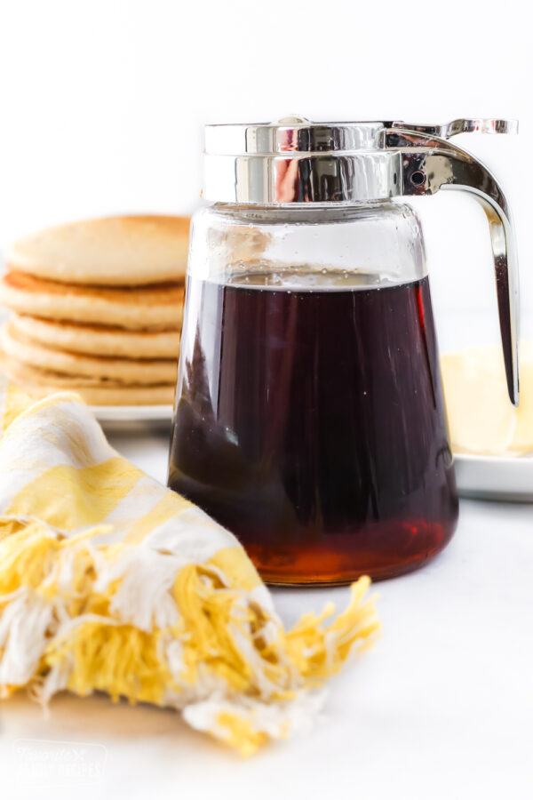 A jar of homemade maple syrup in front of a stack of pancakes and softened butter
