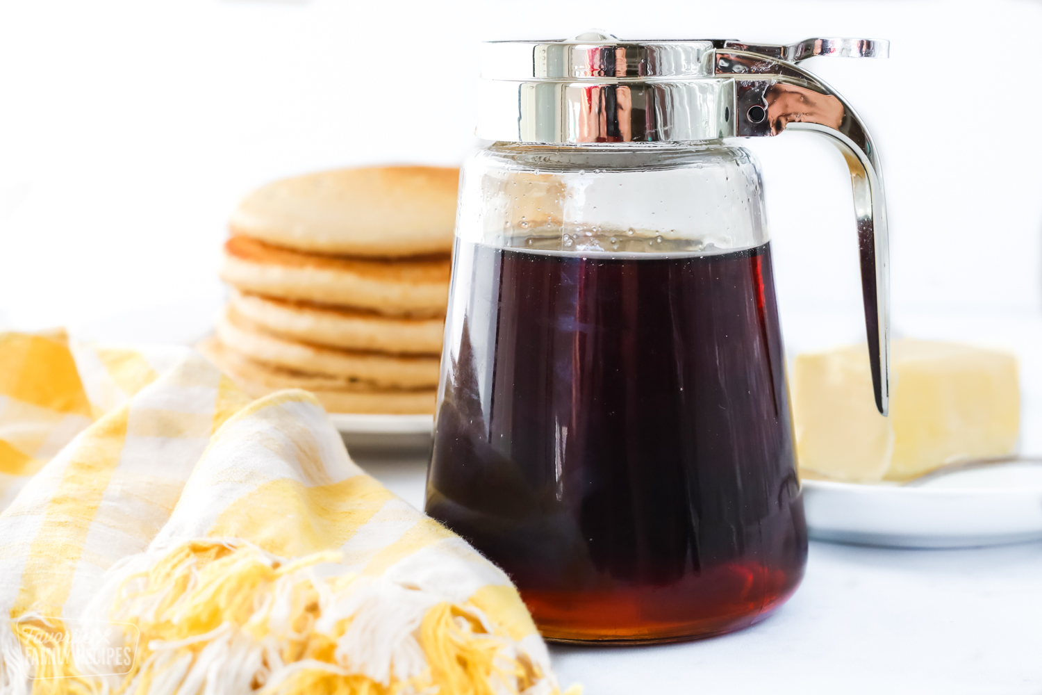 A jar of homemade syrup next to a stack of pancakes and a stick of butter