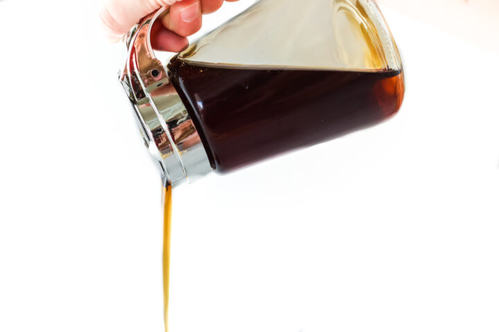 Homemade maple syrup being poured from a lidded syrup jar