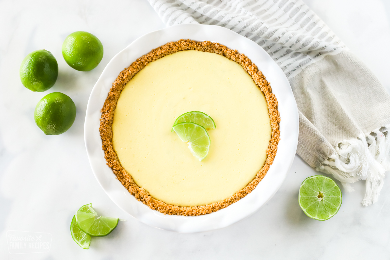 A top view of a fresh key lime pie with lime wedges and whole limes