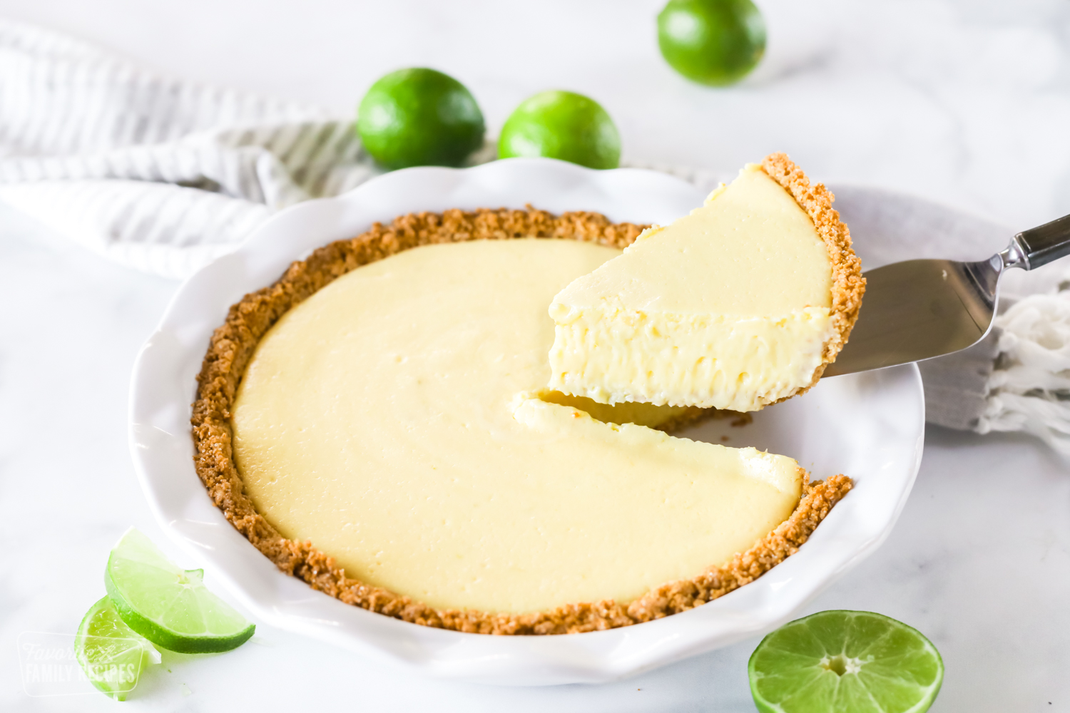 A plain slice of key lime pie being lifted from a pie pan with a pie knife