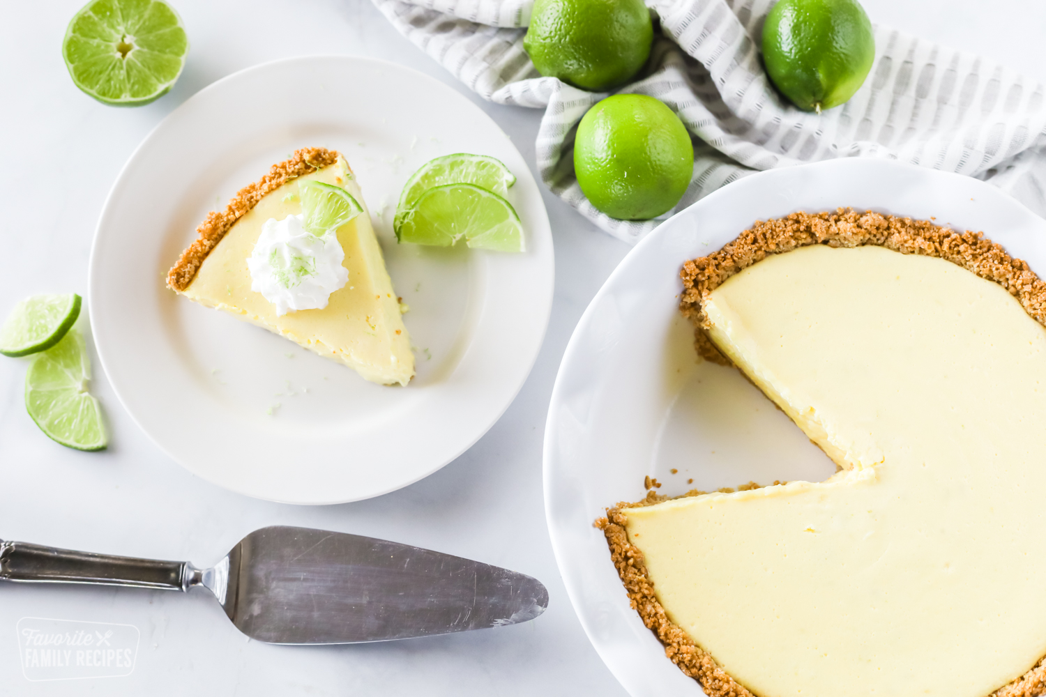 A whole key lime pie made with graham cracker crust and a slice taken out of it with limes as garnishes