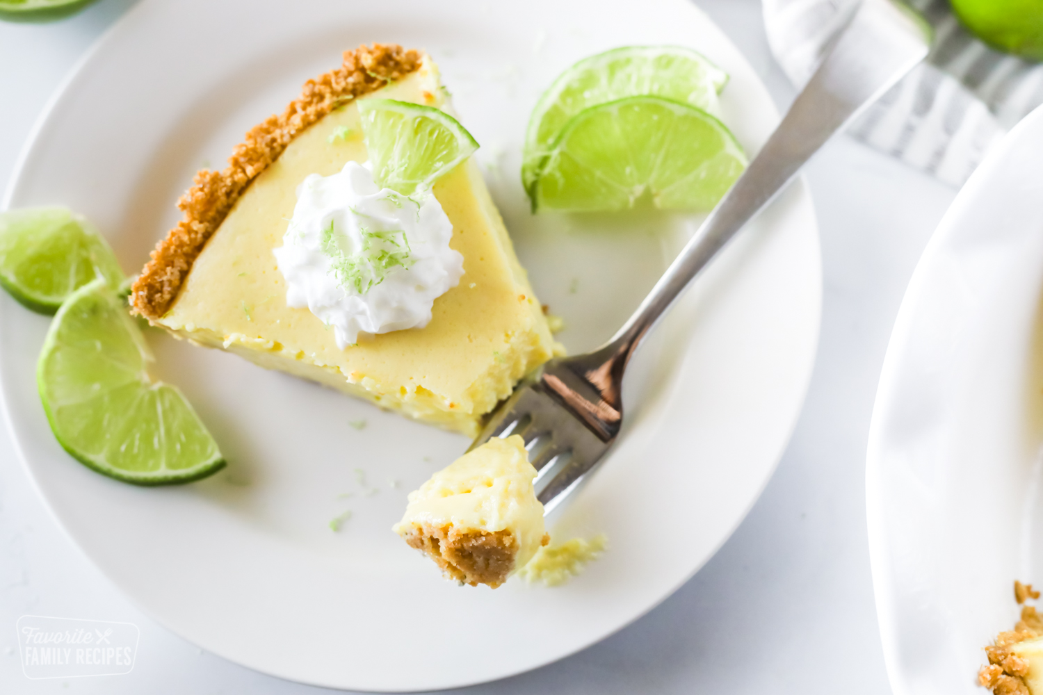 A slice of key lime pie with a graham cracker crust and a bite on a fork