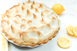 A whole lemon meringue pie shown from the side to see the toasted meringue tips on the topping.