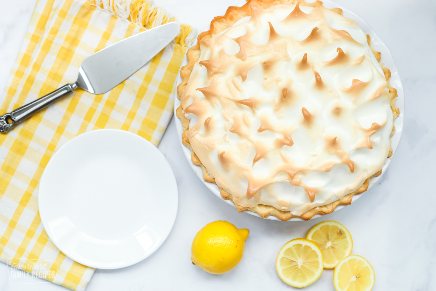 A top view of a whole lemon meringue pie next to a plate, a pie knife, and lemons.