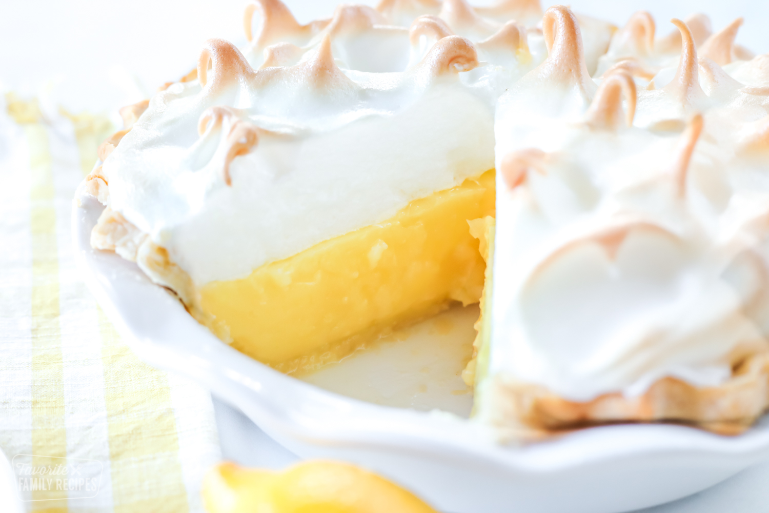 A whole lemon meringue pie in a white pie pan with one slice removed to show lemon layer and crust