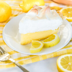A slice of lemon meringue pie on a plate garnished with lemon wedges