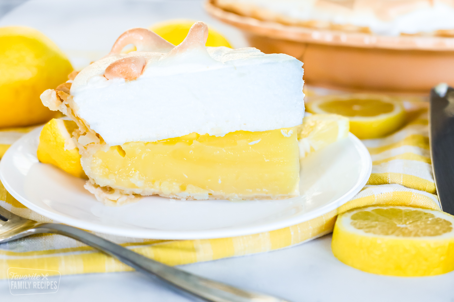 A direct side view of a slice of lemon meringue pie to show the lemon and meringue layers.