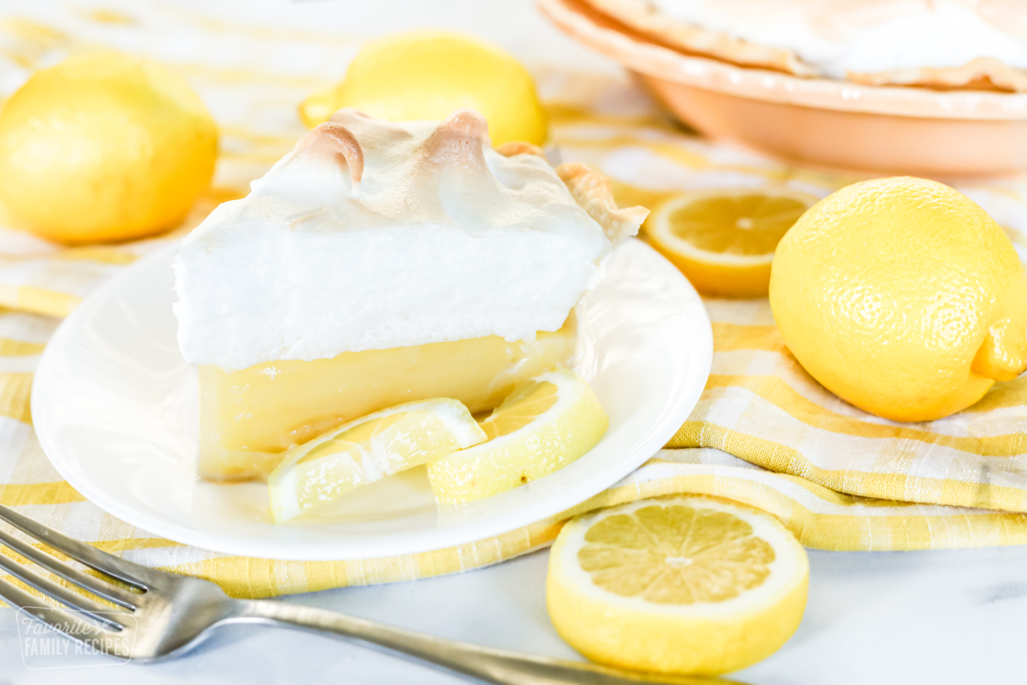 A slice of lemon meringue pie on a plate garnished with lemons. The plate is sitting on a yellow cloth napkin next to a fork and lemons.