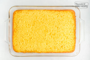 A lemon cake in a glass baking dish with the top leveled