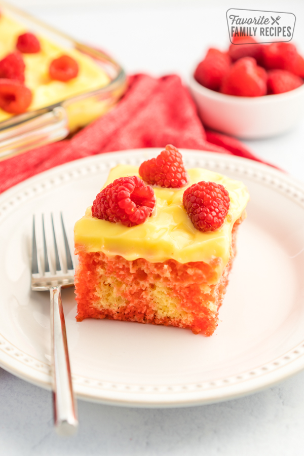 Raspberry Lemon Jello Poke Cake topped with lemon pudding frosting and fresh raspberries