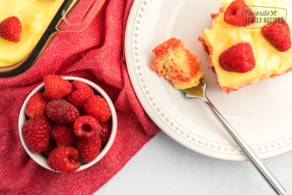 Raspberry Lemon Jello Poke Cake topped with lemon pudding frosting and fresh raspberries