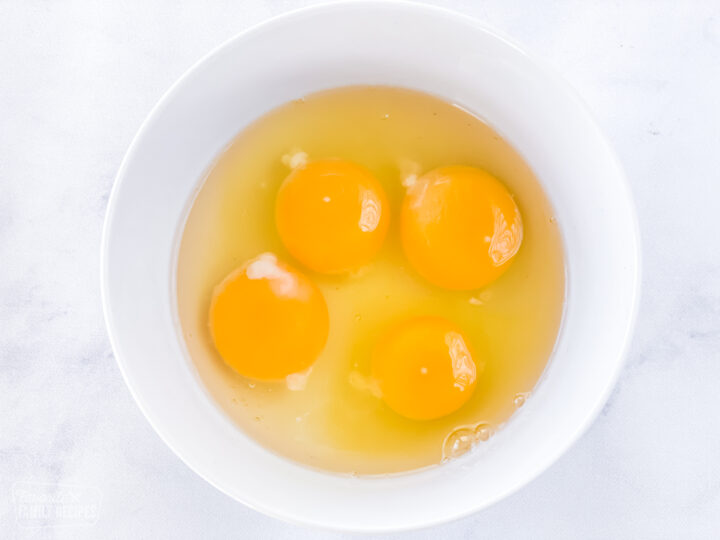 Four egg yolks sitting in eggs whites in a small bowl.