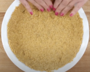 Crushed graham crackers mixed with butter being flattened in a pie dish making a homemade pie crust for key lime pie