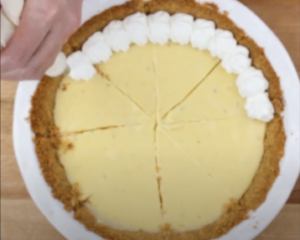 Whipped cream being piped onto key lime pie as a topping