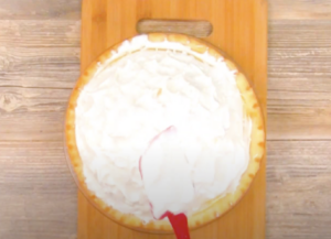 White meringue topping being spread over a lemon meringue pie with a red rubber spatula