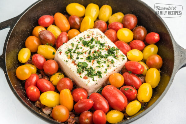 Heirloom cherry tomatoes and a block of feta cheese in a cast iron skillet
