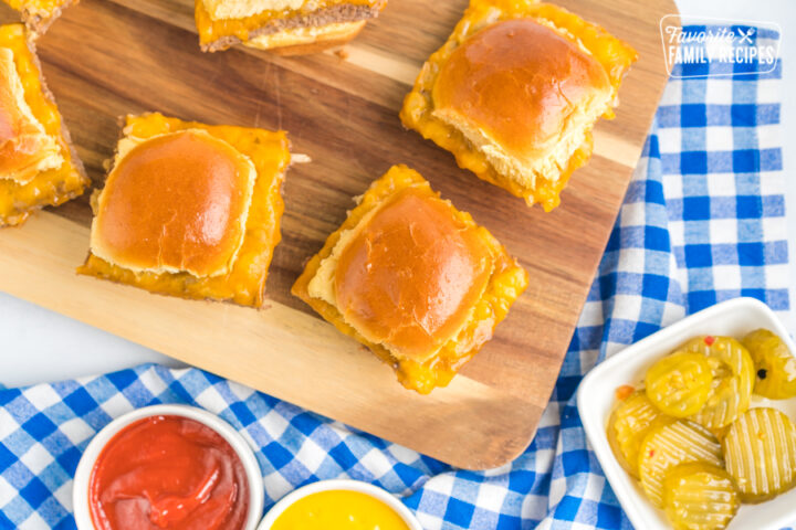 White Castle Sliders on a cutting board with little bowls of ketchup, mustard, and pickles