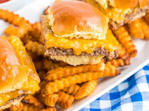 A serving dish filled with french fries and topped with three White Castle Sliders