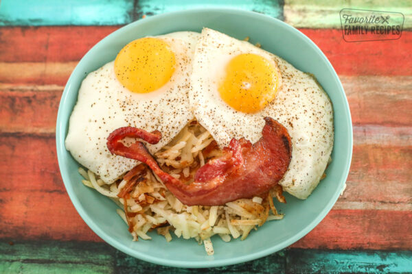 Hashbrowns, 2 eggs, and bacon in a bowl making a smiley face