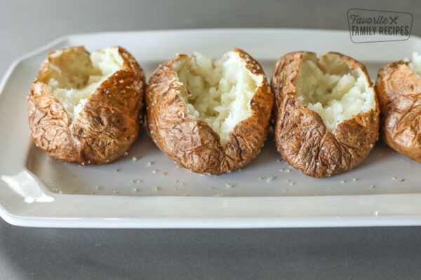 Row of baked potatoes that have been opened and mashed inside.
