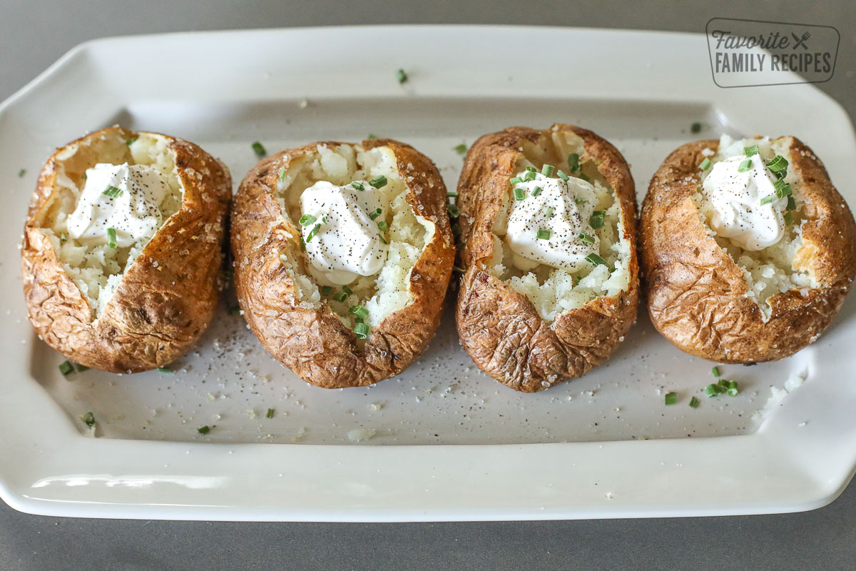 Baked potatoes on a platter with sour cream and chives.