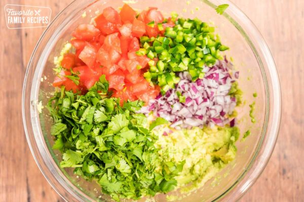 Mashed avocado, diced tomatoes, diced red onions, cilantro, and diced jalapeno in a large glass bowl