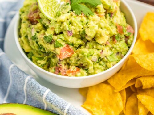 Guacamole in a small bowl topped with a lime slice and a cilantro leaf