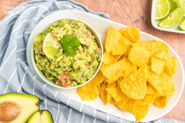 A small bowl of guacamole topped with a slice of lime and a cilantro leave. The bowl is next to a pile of tortilla chips.