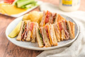 A club sandwich served on a plate with potato chips and a pickle