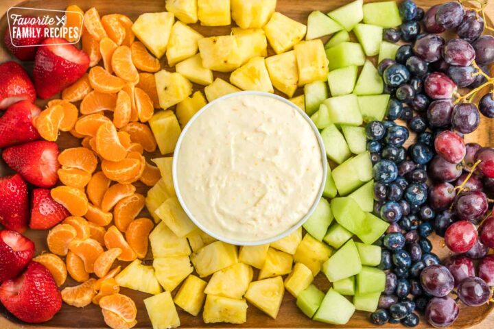 A tray full of fruit with a bowl of fruit dip