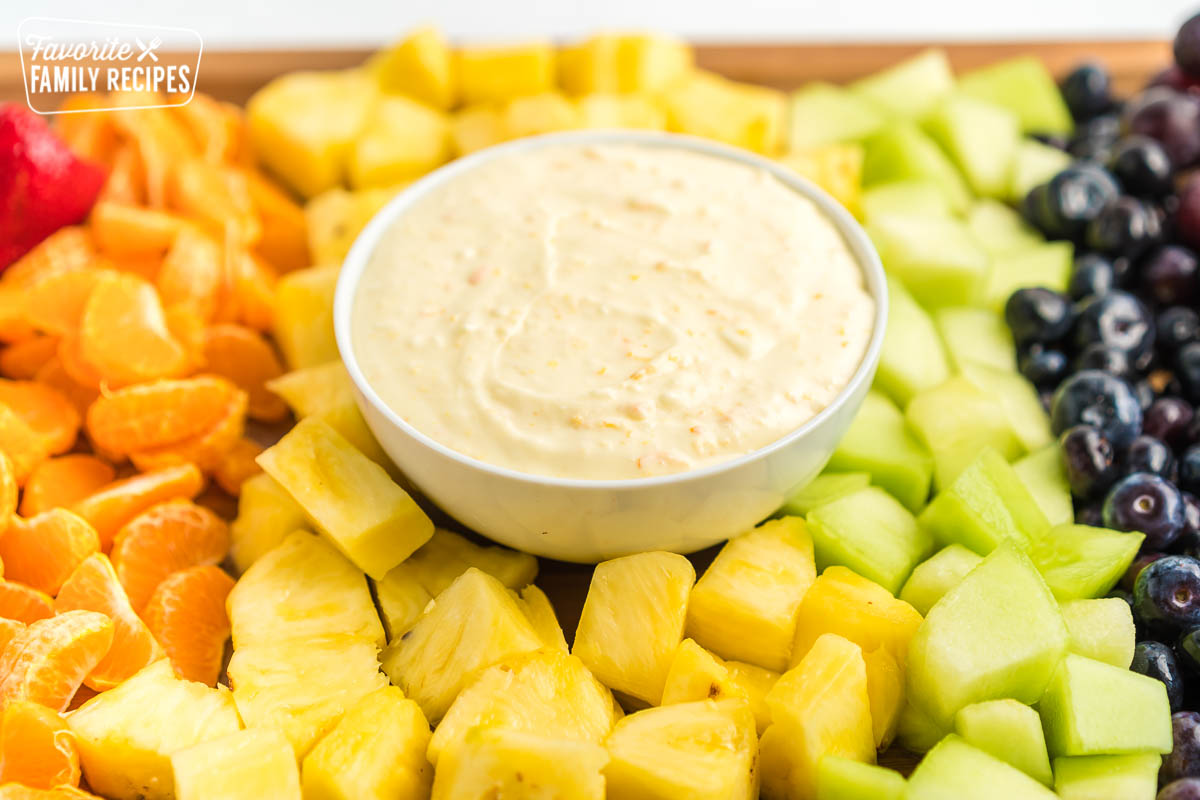 A bowl of fruit dip surrounded by different cut up fruits