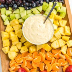 A bowl of fruit dip surrounded by fruit
