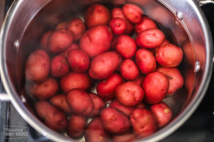 Small red potatoes in a bot of water on a stovetop.