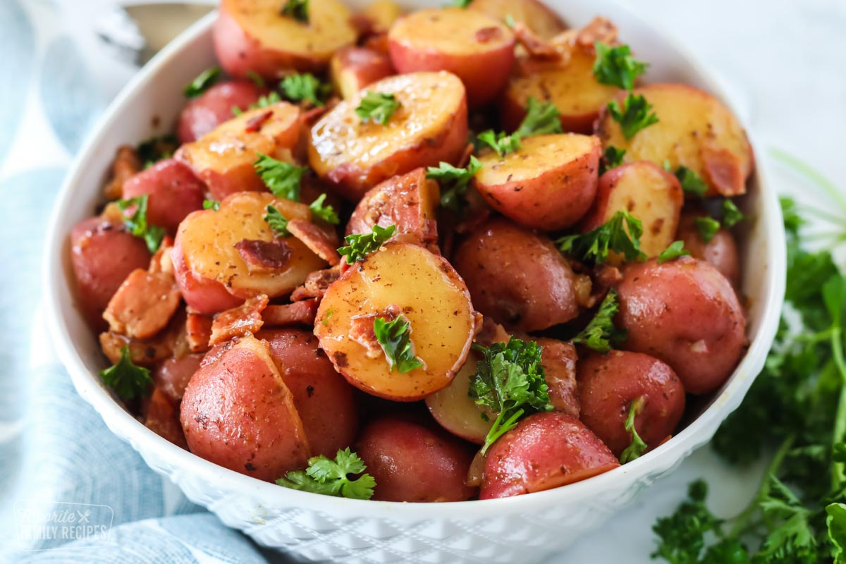 A bowl of halved red potatoes with a bacon vinegar glaze, garnished with parsley and bacon bits combined to make German Potato Salad.