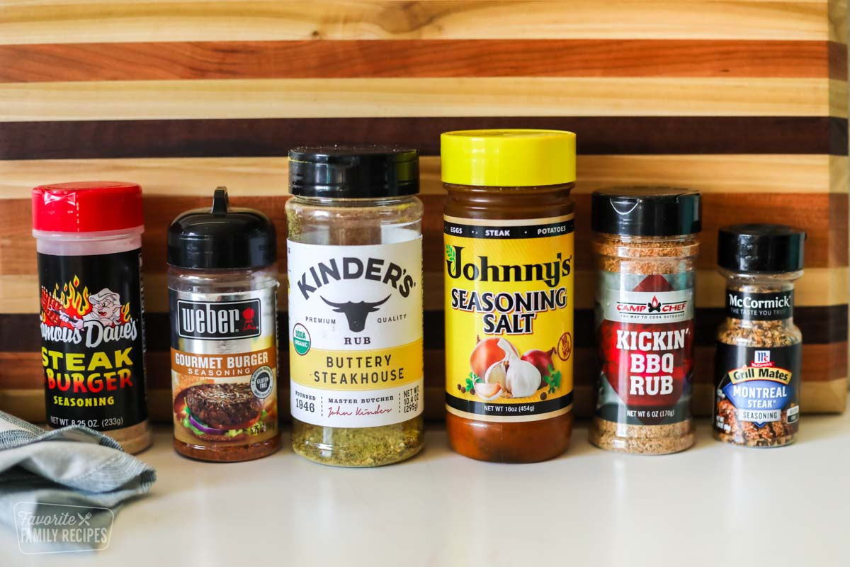 Six different hamburger seasonings lined up in front of a cutting board.