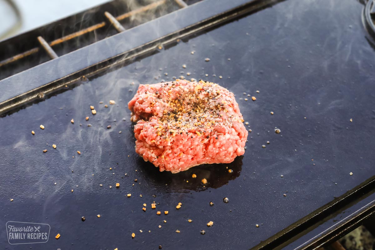 Ground beef on a cast iron griddle with seasonings