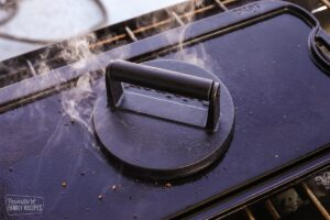 A cast iron burger press pressing down on a hamburger over the grill