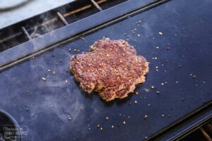 A hamburger patty cooking on the grill with seasonings on top