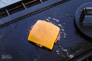 A hamburger patty on the grill with a slice of cheese over the top