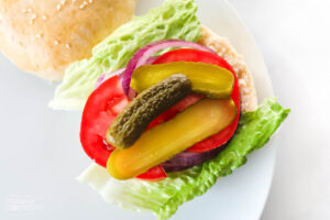 An open faced hamburger bun layered with lettuce, tomatoes, pickles and sliced onion over the top