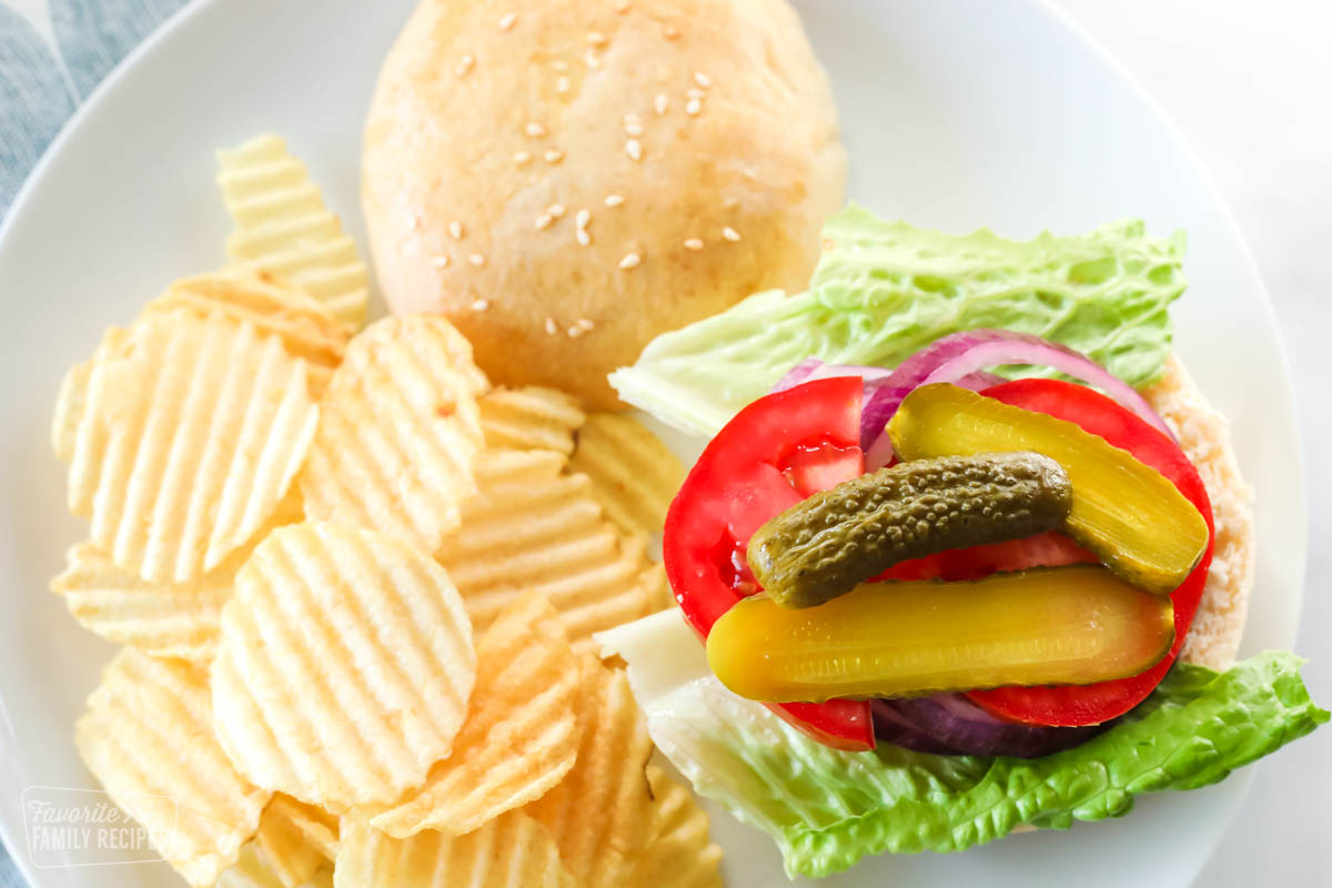 An open faced hamburger bun with lettuce, tomato, onions, and pickles on a plate
